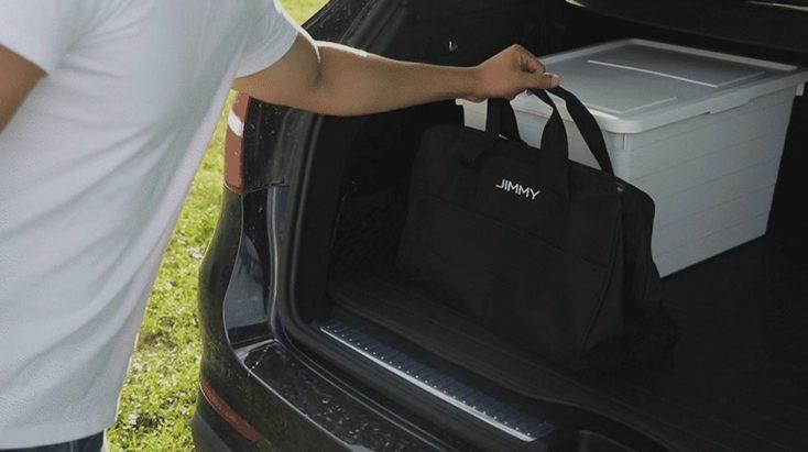 modelo coge la bolsa de transporte Jimmy del maletero del coche