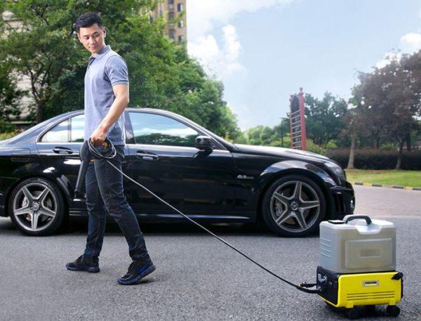 moelo con el cable estirado del Xiaomi Kärcher, cerca de un coche recién limpiado