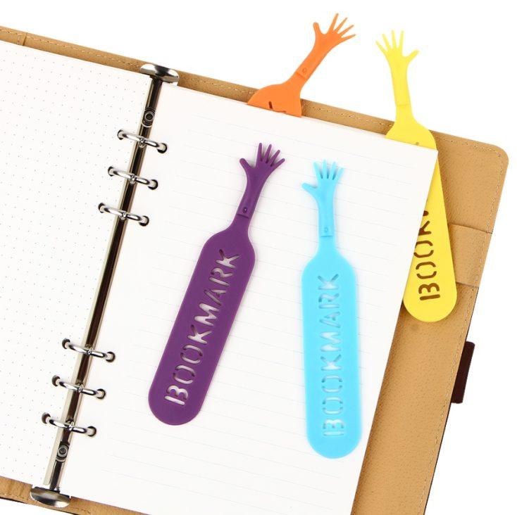 Marcapáginas en diferentes colores sobre y metido en un cuaderno de notas