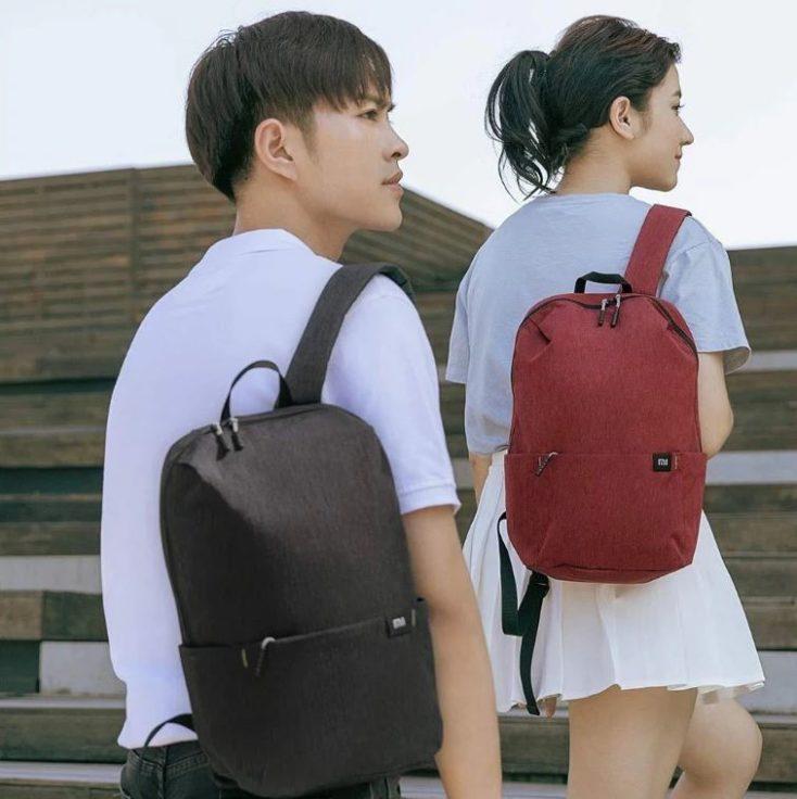 dos modelos con la mochila una chica con la mochila en granate y un chico con la mochila en negro