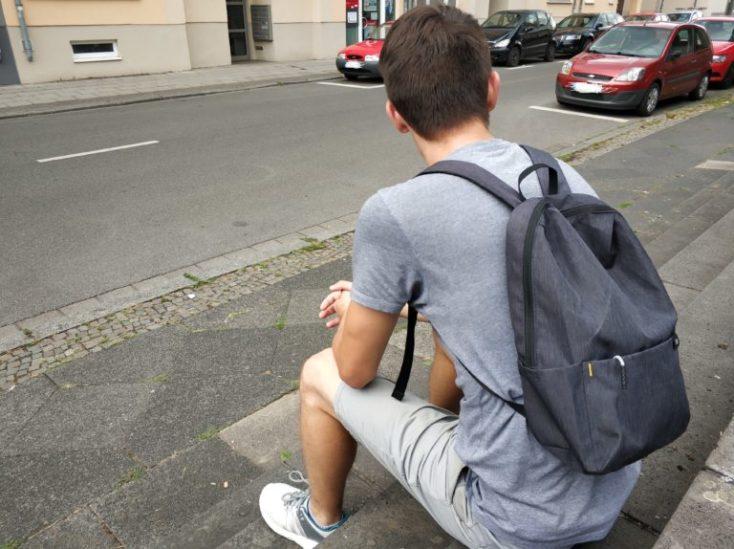 yo sentado en unos escalones con la mochila puesta
