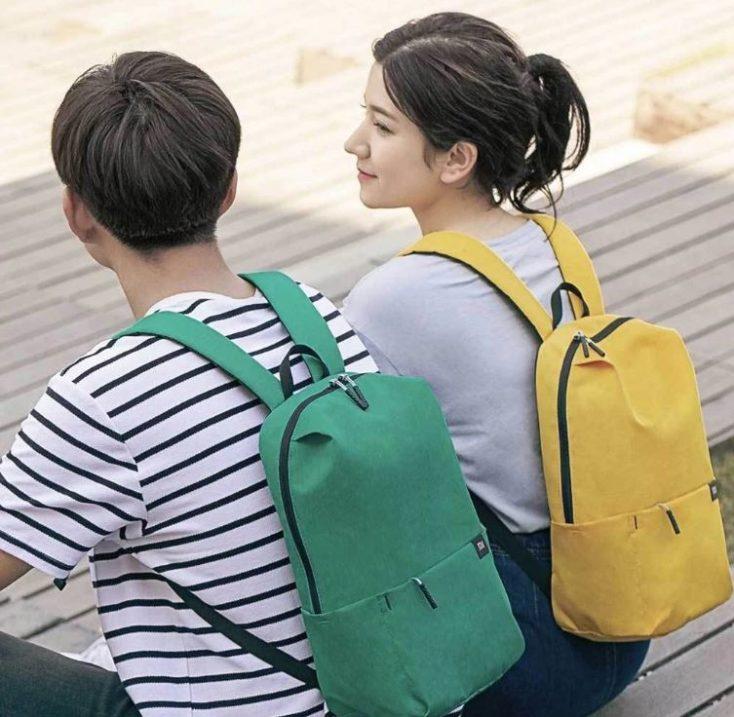 dos modelos sentados con la mochila una chica con la mochila en amarillo y un chico con la mochila en verde