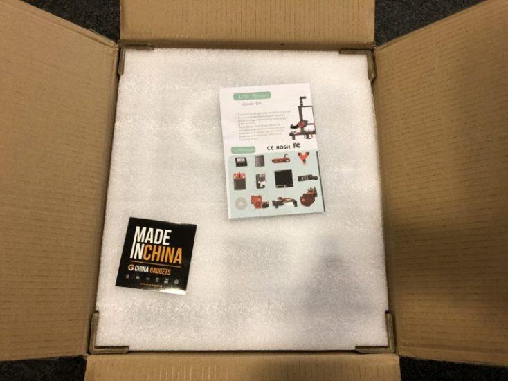 paquete abierto con las instrucciones, nuestra pegatina y una espuma protectora de embalaje.