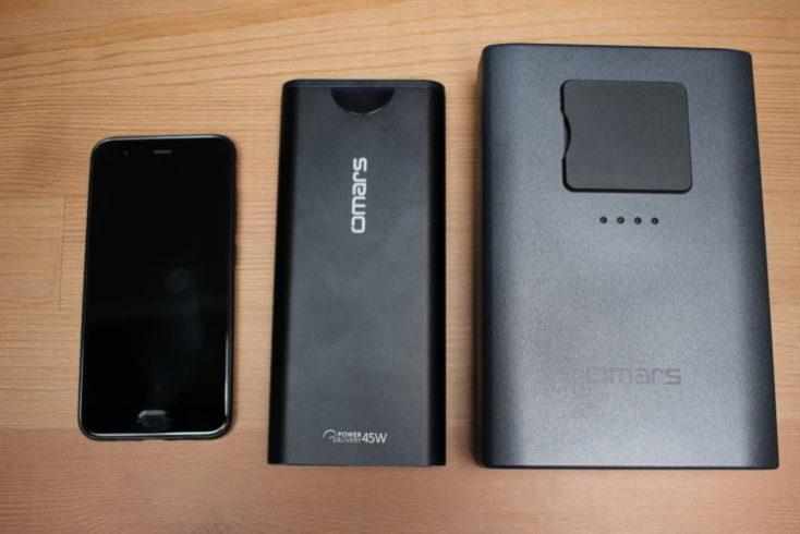 Comparqación del tamaño de la batería externa Omars de 40200 mAh junto a otra batería externa y un smartphone