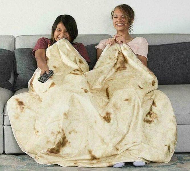Dos chicas cen el sofá con la manta burrito