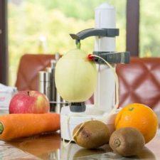 Pelador eléctrico pelando una pera y con frutas y una zanahoria alrededor