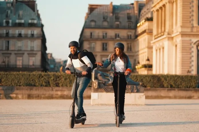 2 personas montando en el patinete eléctriconinebot Max