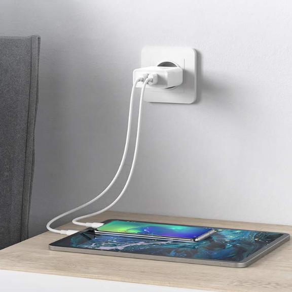 Cargador USB DE 2 puertos enchufado, cargando una tablet y un móvil