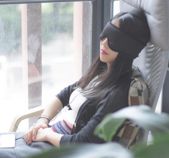 Mujer durmiendo en un sillón con el antifaz para dormir de Xiaomi.