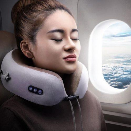 Mujer con el cojín masajeador cevical en el avión