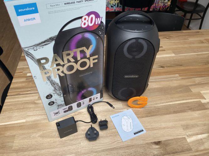Altavoz bluetooth Anker Soundcore Rave Mini, al lado su caja y los accesorios incluidos