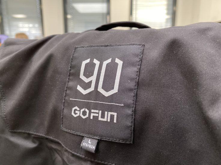 Etiqueta de la talla y logo de la chaqueta de plumas 90FUN con sistema de calefacción