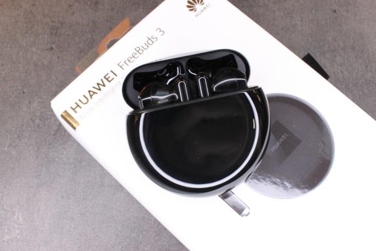 auriculares Huawei FreeBuds 3 en la funda de carga, encima de su caja