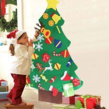 Niña decorando el árbol de Navidad de fieltro