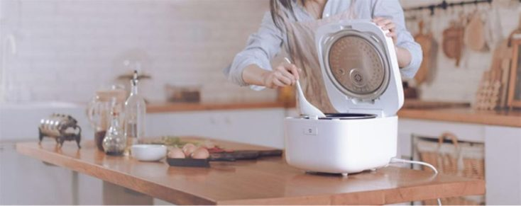 Mujer cocinando con la arrocera eléctrica Xiaomi
