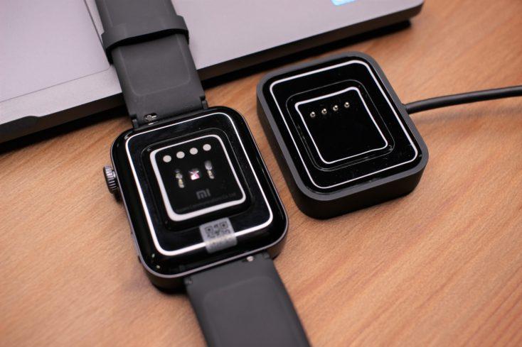 Parte de abajo del Xiaomi Mi Watch y al lado su cargador