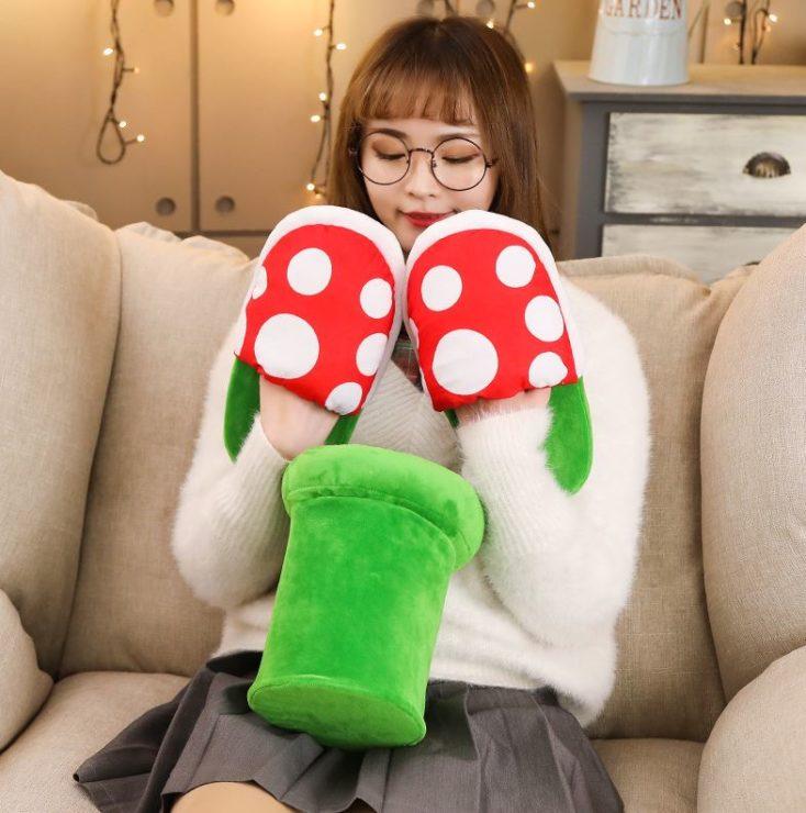 chica con las zapatilas para casa con diseño de planta piraña en las manos y la pipa verde