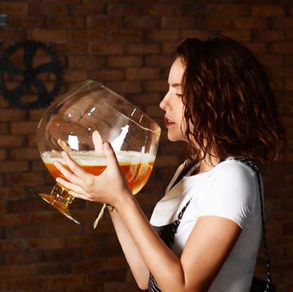 Chica bebiendo cerveza de la copa de vino gigante