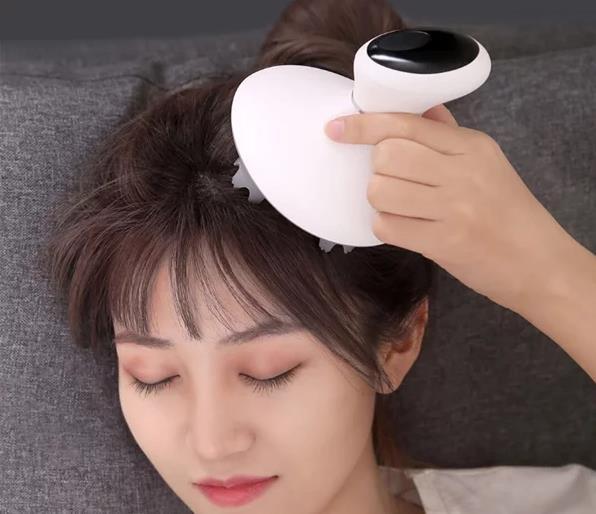 Mini masajeador de cabeza de Xiaomi en la cabeza de una chica