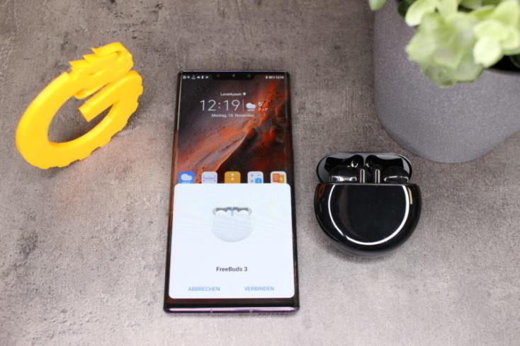 Auriculares bluetooth Huawei FreeBuds 3 en la funda de carga al lado del Huawei Mate 30 Pro30
