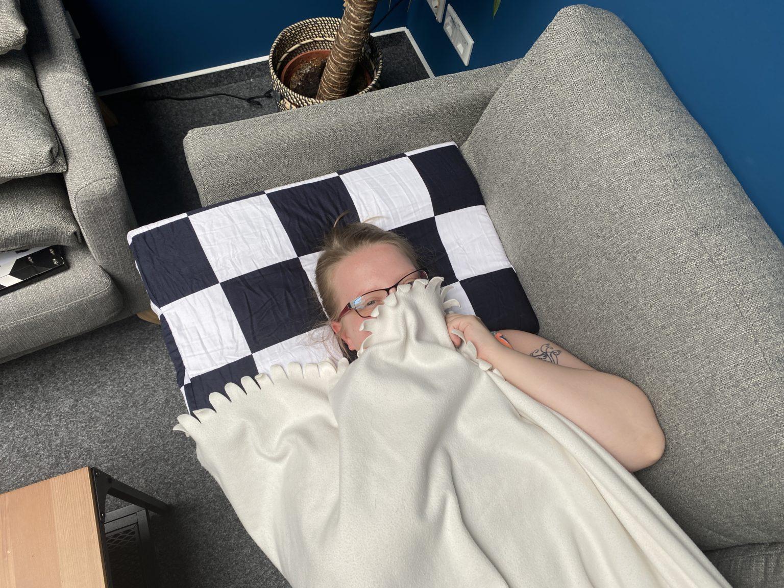 Durmiendo sobre la almohada viscoelastica modular de U2 tapada con una manta