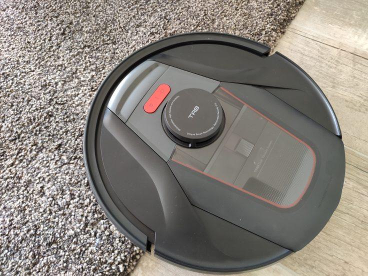 Robot aspirador Haier Tab Tabot subiendo por la esquina de una alfombra gorda