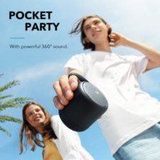 Chico sujetando el altavoz Bluetooth Soundcore Mini 3 con el cordon